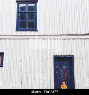 Noruega, Fredrikstad, Boy (10-11) sentada contra house