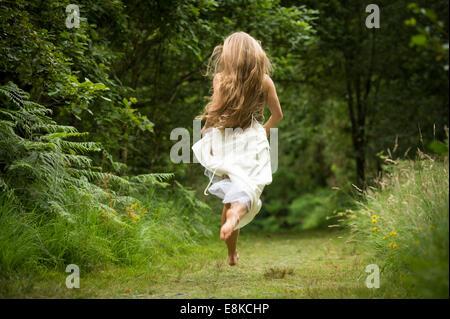 Runaway bride, vista trasera de una mujer joven y saludable slim caucásica chica con largo pelo rubio salir corriendo en un camino en el bosque bosque vestidas de blanco vestido de novia levita en el campo UK