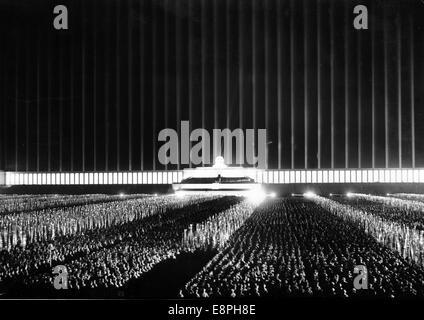 """Nuremberg Rally 1937 en Nuremberg, Alemania - Vista de la votación nominal de los dirigentes políticos del partido Nazi (NSDAP) en el campo Zeppelin en el partido nazi rally motivos. La propaganda original de texto! Los informes de noticias de los nazis en la parte posterior de la imagen: """"La gran nominal de los líderes políticos tuvieron lugar esta noche, 110.000 de los cuales habían caído en la formación en doce enormes bloques. Los reflectores de repente estalló y creado una fantástica sinfonía de color en una abrumadora rapto de luz en color marrón y rojo y blanco, en reluciente oro y plata. Nuestra imagen: El iluminado mágicamente Ze"""