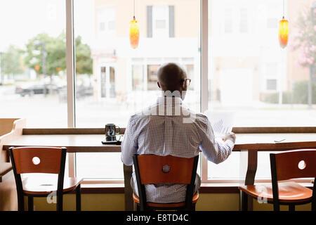 Hombre Negro leyendo el papeleo en la cafetería.