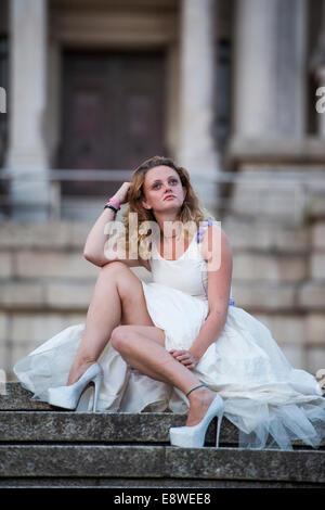 El Runaway o jilted bride - una joven vestida con un traje de novia triste sentada sola en la escalera de piedra, la noche afuera uk
