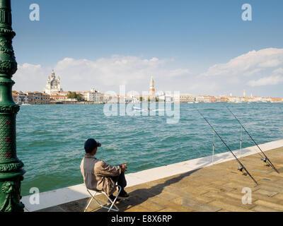 Un pescador esperando pacientemente para pescar, con vistas al Canale della Giudecca en Venecia, Italia.