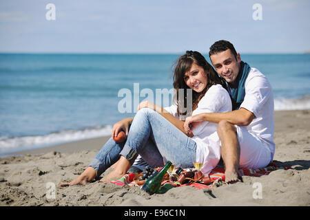 Pareja joven disfrutando de un picnic en la playa