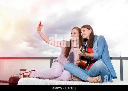 Dos jóvenes mujeres teniendo autorretrato con smart phone, Munich, Baviera, Alemania