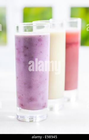Un vaso de crema de yogur mezclado Berry smoothie con una variedad de otros sabores en una fila se aleja con poca dof