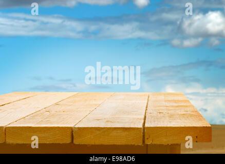 Mesa de madera vacías contra un cielo azul con nubes blancas mullidas para la colocación de su alimento o producto