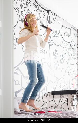Emocionada chica escuchando música mientras canta con cepillo en casa