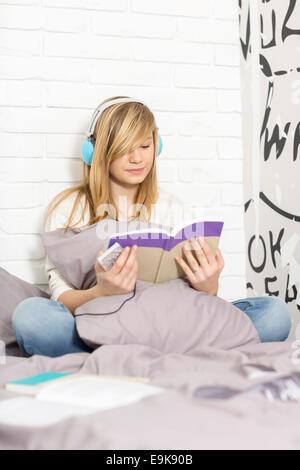 Longitud completa de adolescente escuchando música mientras libro de lectura en el dormitorio