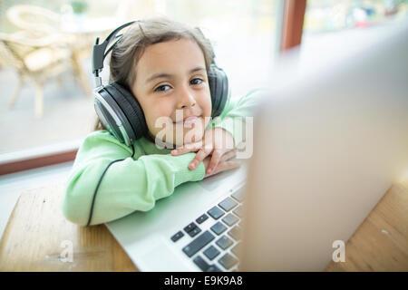 Retrato de linda niña escucha música con los auriculares con la laptop en la mesa