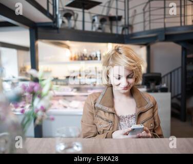 Feliz joven leer mensaje de texto por teléfono celular en la cafetería