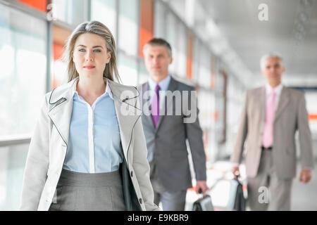 Hermosa joven empresaria caminando con sus colegas masculinos en el fondo en la plataforma de tren
