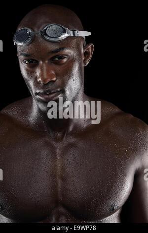 Determinado nadador con cuerpo mojado mirando a la cámara. Retrato de joven atleta masculino afroamericano con cuerpo musculoso.
