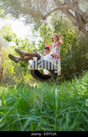 Dos niñas sentado y de pie en el giro del árbol en el jardín