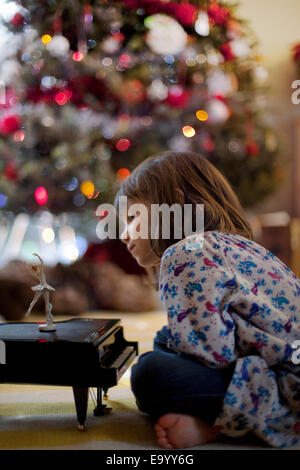 Chica sentada en el suelo del cuarto de estar escuchando música de piano de juguete en Navidad caja