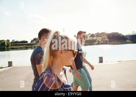 Cuatro jóvenes amigos caminando a lo largo de Riverside Foto de stock