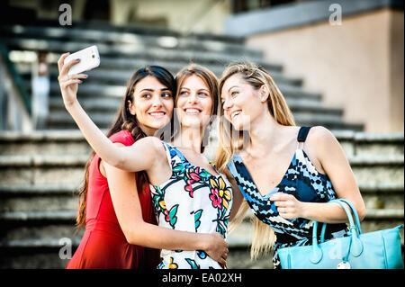 Tres jóvenes mujeres teniendo selfie moda en escalera, Cagliari, Cerdeña, Italia