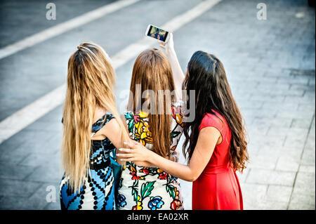 Vista trasera de tres jóvenes mujeres teniendo selfie con el smartphone, Cagliari, Cerdeña, Italia