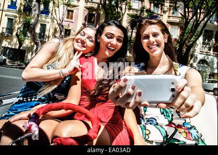 Tres jóvenes mujeres teniendo selfie smartphone en la calle, Cagliari, Cerdeña, Italia
