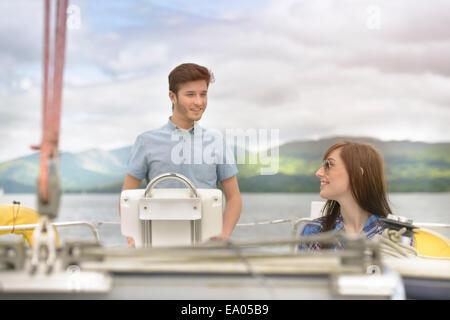 Pareja joven navegando en velero por el lago Foto de stock