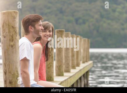 Pareja joven riendo juntos en el embarcadero del lago