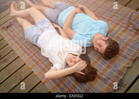 Sonriente joven pareja acostado sobre una manta en el embarcadero