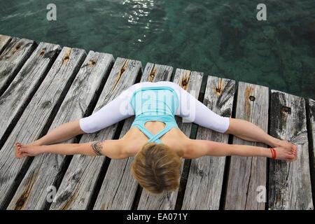 Vista aérea de mediados de mujer adulta con brazos y piernas extendidas practicando yoga en Mar del muelle de madera