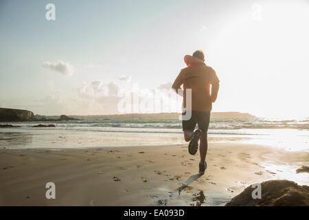 Hombre maduro corriendo en la arena, a lo largo de la costa
