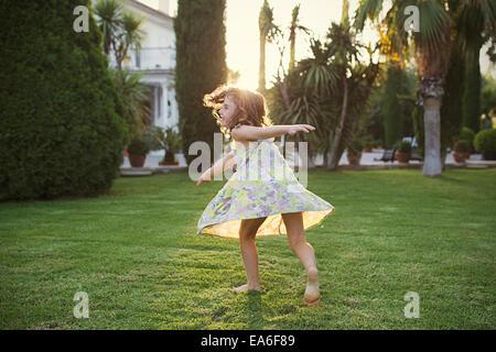 Chica están girando alrededor en el jardín Foto de stock