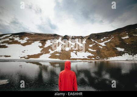 Vista posterior del joven mirando al lago de montaña