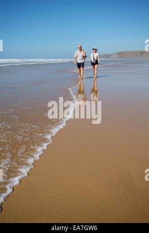Par caminando Waters Edge en la playa durante la marea baja de Watergate Bay en el norte de la costa de Cornwall Foto de stock
