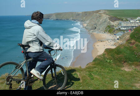 Ciclista en acantilado mirando hacia la playa con peaple sobre la arena y el surf en el mar cerca de Newquay Restormel Foto de stock