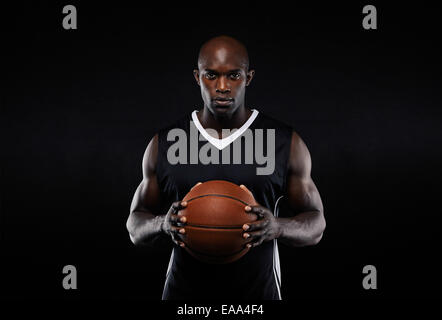 Retrato del joven jugador de baloncesto masculino muscular en uniforme con una pelota de baloncesto posando sobre fondo negro