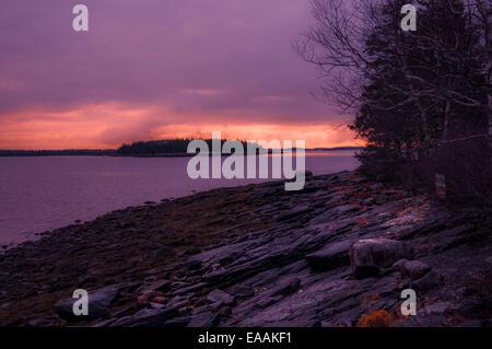 Mirando a lo largo de una playa rocosa de una puesta de sol, el área entre el horizonte y las nubes iluminadas con luz rosa anaranjado fuerte