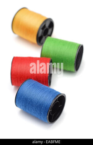 Cuatro bobinas de hilo de color aislado en blanco