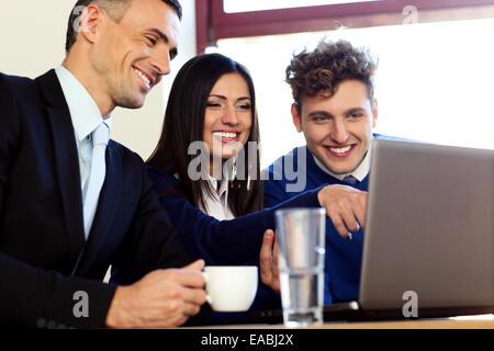 Sonriendo gente de negocios trabajando en el portátil.