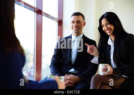 Empresarios sonrientes tener coffee break en la oficina