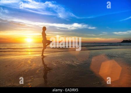 Mujer joven haciendo fitness en Ocean Beach durante el increíble atardecer.
