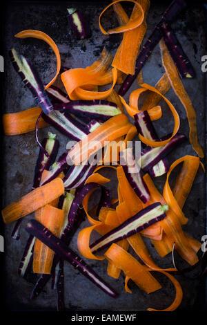 Morado y naranja zanahorias, afeitado, en bandeja oscura