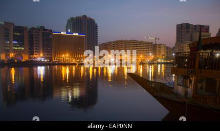 Altos edificios contra el cielo teñido de rosa y las luces brillantes de la ciudad reflejada en la oscuridad de Foto de stock