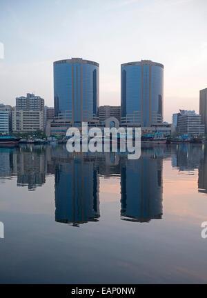 Dos idénticos modernos rascacielos, pequeñas nubes rosadas y los edificios de la ciudad se refleja en las aguas Foto de stock
