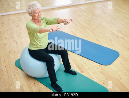 Jefa sentada sobre una pelota de gimnasia y levantamiento de pesas. Anciana el ejercicio con pesas en el gimnasio.