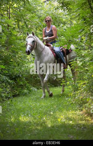 Mujer caucásica en caballo en el ámbito rural
