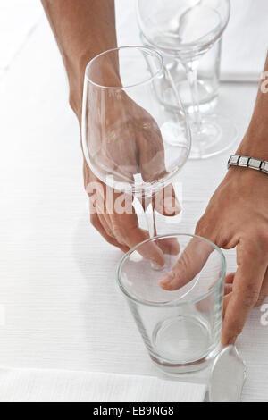 Cerca de las manos del camarero organizar gafas de mesa de restaurante