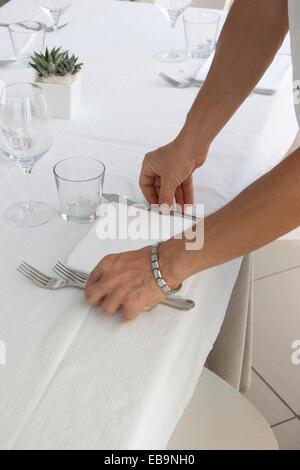 Cerca de las manos del camarero organizar cubiertos de mesa de restaurante