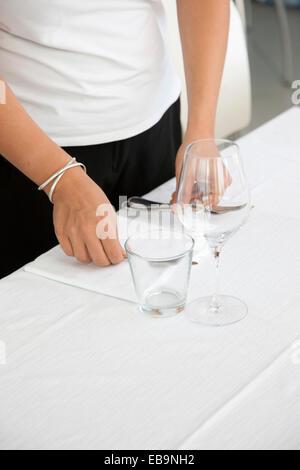 Cerca de las manos de camarera arreglando cubiertos de mesa de restaurante