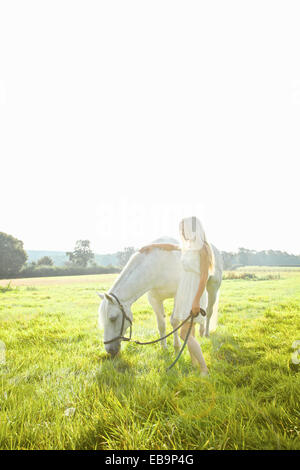 Mujer joven acariciar a caballo en el campo Foto de stock