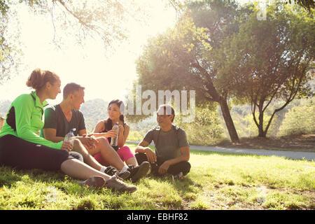 Cuatro machos y hembras maduras corredores sentados conversando en el parque Foto de stock