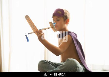 Muchacho de capa y máscara jugando con avión de juguete en casa Foto de stock