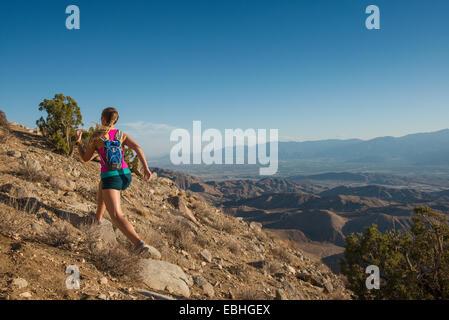 Mujer corriendo en montaña, el Parque Nacional Joshua Tree National Park, California, EE.UU.