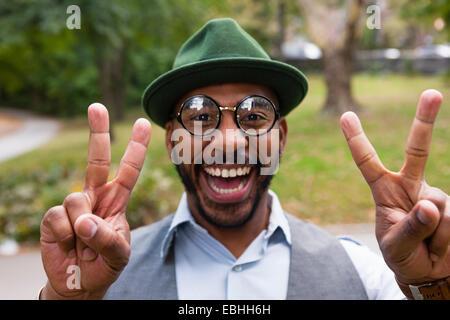 Hombre, haciendo la paz firmar sonriendo ampliamente en park